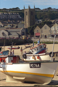 Church overlooking beached fishing boats in St Ives harbour at low tide